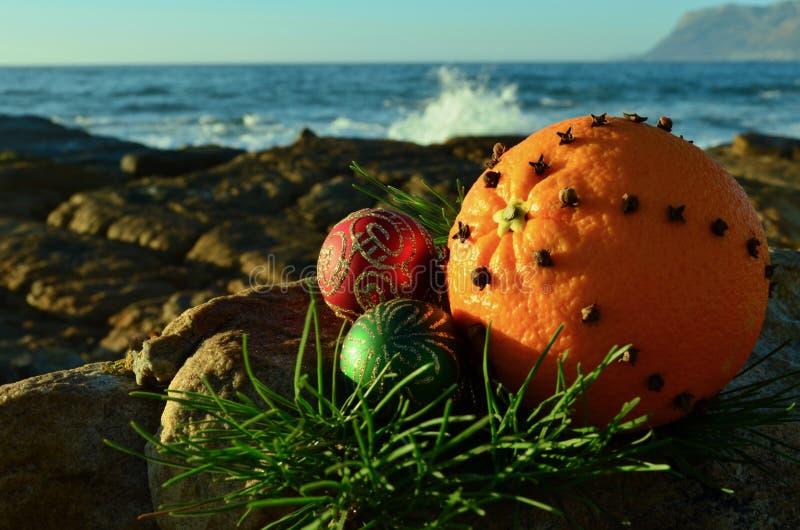 Bożenarodzeniowa goździkowa pikantność gwożdżąca pomarańczowa owoc na rockowej czerwieni i zieleń połyskujemy dekoracje Bożenarod obrazy stock