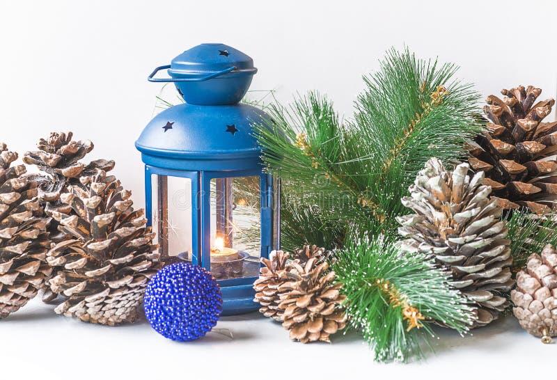Bożenarodzeniowa kartka z pozdrowieniami z lampionem, sosna rożkami i gałąź błękitnymi, obrazy stock