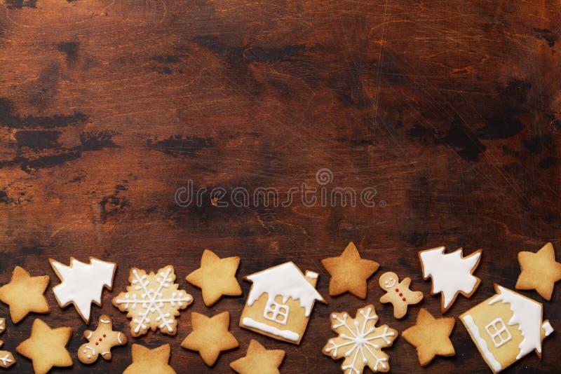 Bożenarodzeniowa kartka z pozdrowieniami z piernikowymi ciastkami na drewnianym tle Odgórny widok z przestrzenią dla twój powitań fotografia stock