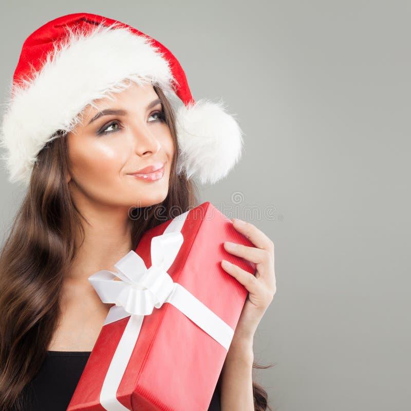Bożenarodzeniowa kobieta w Santa kapeluszu z Czerwonym Xmas prezenta pudełkiem obraz stock