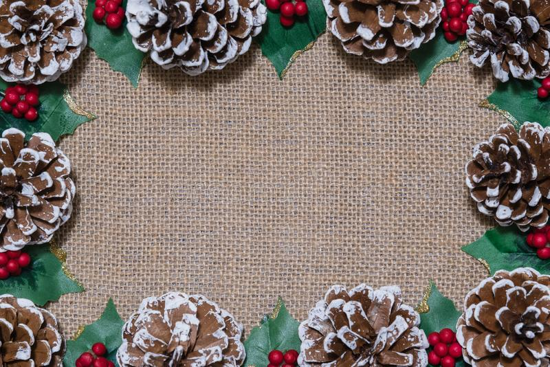 Bożenarodzeniowa Lay rama pinecones, uświęconi liście i czerwone jagody na nieociosanym tkaniny tle, zdjęcia royalty free