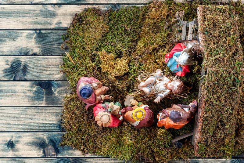 Bożenarodzeniowa narodzenie jezusa scena z Świętą rodziną w budzie i trzy mędrzec stary drewniany tło zdjęcia stock