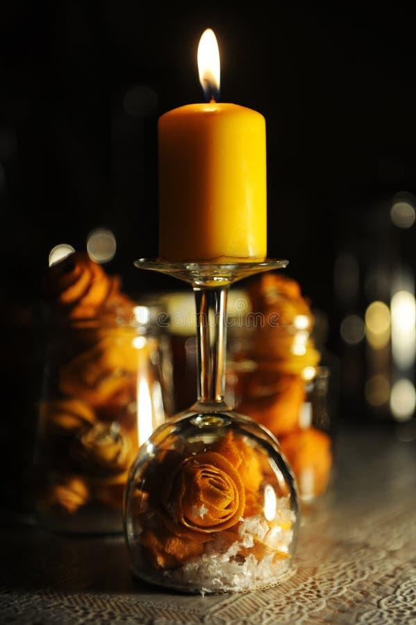 Bożenarodzeniowa płonąca pomarańczowa świeczka Tangerine łupy róże i sztuczny śnieg wśrodku przestawnego wina szkła fotografia royalty free
