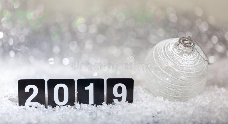 Bożenarodzeniowa piłka i nowy rok 2019, na śniegu, abstrakcjonistyczny bokeh świateł tło fotografia stock