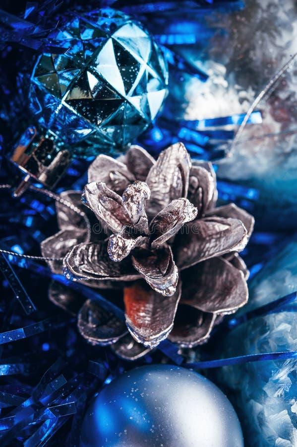 Bożenarodzeniowa piłka z błękitem i srebnej sosny rożkiem błyska obraz stock