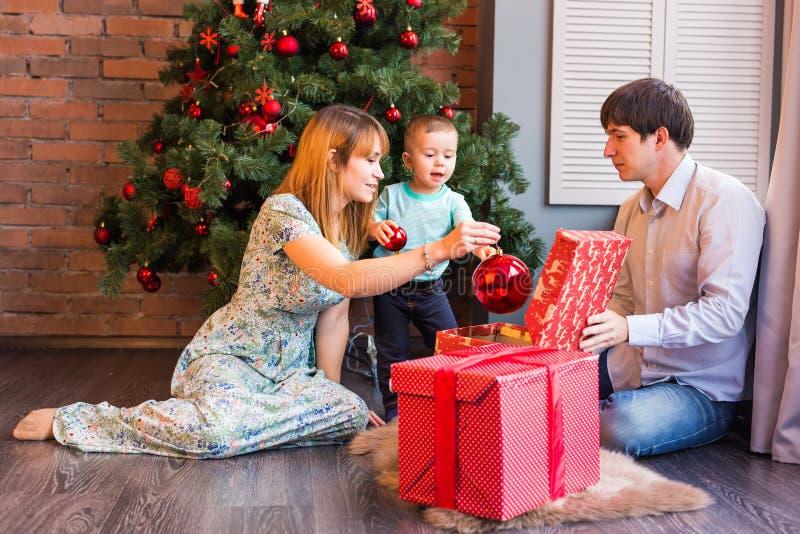 Bożenarodzeniowa rodzina z dzieckiem Szczęśliwy dziecka otwarcia prezent Święta moje portfolio drzewna wersja nosicieli fotografia stock