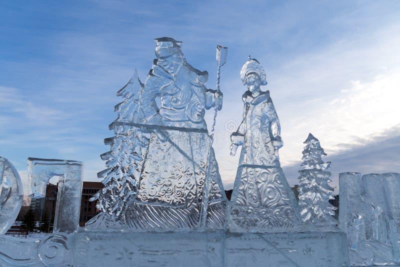 Bożenarodzeniowa rzeźba ojca mróz i Śnieżna dziewczyna, rzeźbiąca z lodu, stoi outside przeciw niebu obraz stock