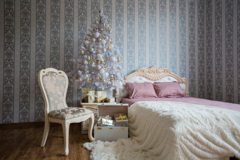 Bożenarodzeniowa scena z łóżkiem, choinką, prezentami i krzesłem, obraz royalty free