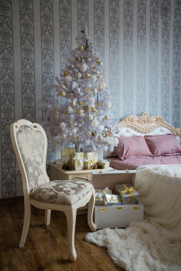 Bożenarodzeniowa scena z łóżkiem, choinką, prezentami i krzesłem, zdjęcia stock