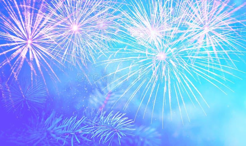 Bożenarodzeniowa sosny gałąź na pięknym błękitnym tle z iskrami i fajerwerkami bryzga, cudowny nowego roku nastrój obrazy royalty free