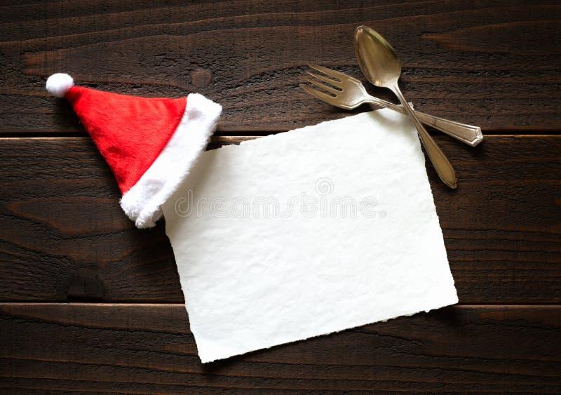 Bożenarodzeniowa Wakacyjna Papierowa karta z, łyżka na Ciemnym Nieociosanym drewno stołu tle Czerwonym i Białymi Święty Mikołaj r zdjęcia stock