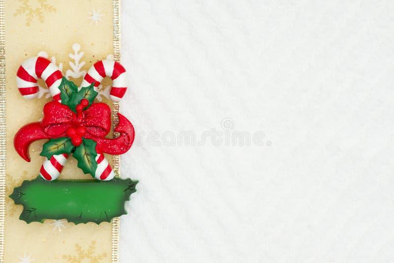 Bożenarodzeniowe cukierek trzciny z łękiem z złocistym faborkiem na białym szewronie textured tkaniny tło obraz stock