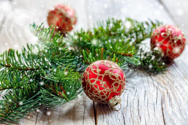 Bożenarodzeniowe czerwone piłki z złocistymi ornamentami i świerczyna rozgałęziają się obraz royalty free