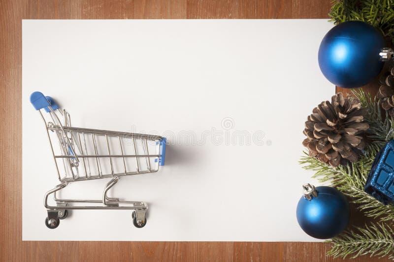 Bożenarodzeniowe dekoracje na drewnianym stole i dużej biel karcie z wózkiem na zakupy na nim jako kopii przestrzeń zdjęcie royalty free