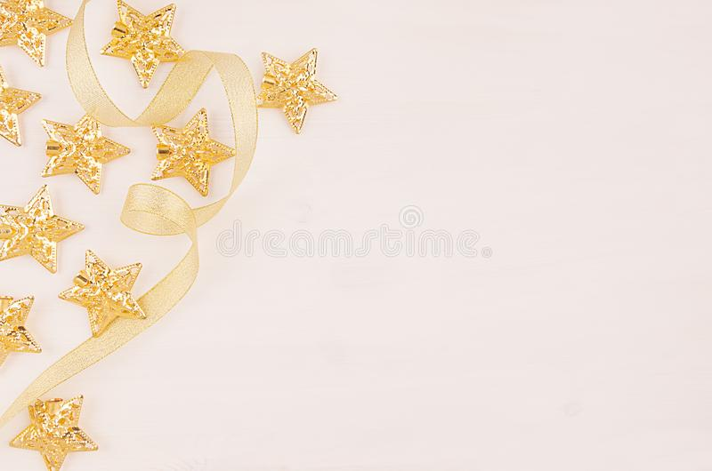 Bożenarodzeniowe dekoracje, złocistych gwiazd skarbikowany faborek na miękkim białym drewnianym tle, kopii przestrzeń obrazy royalty free