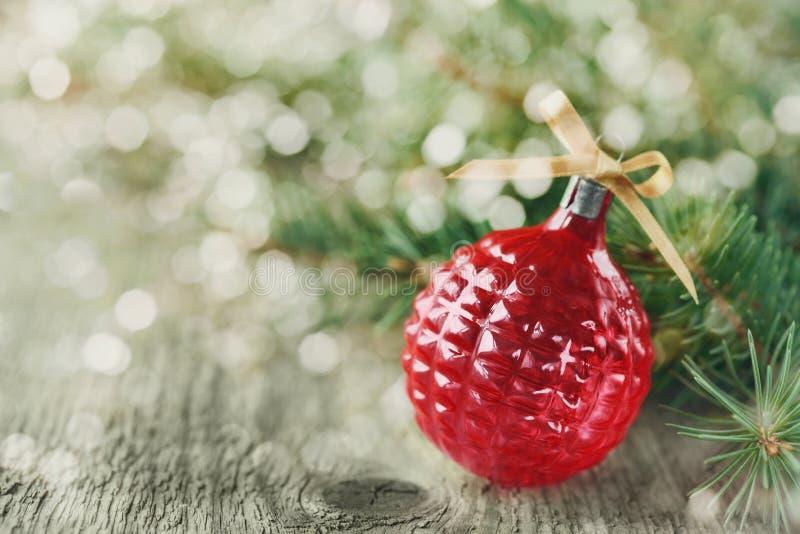 Bożenarodzeniowe dekoracje z czerwoną Bożenarodzeniową piłką i jedlinowe gałąź na drewnianym tle z magicznym bokeh skutkiem, kart zdjęcia royalty free
