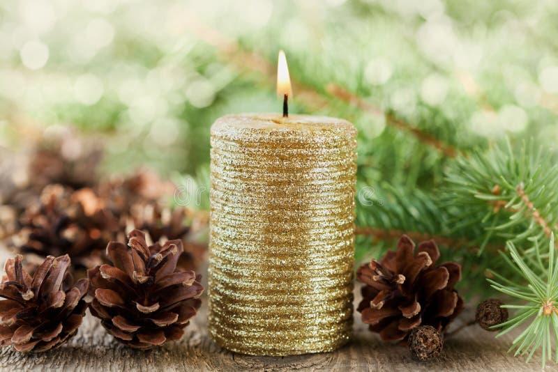 Bożenarodzeniowe dekoracje z zaświecającą świeczką, sosna rożkami i jedlinowymi gałąź na drewnianym tle z magicznym bokeh skutkie obrazy stock