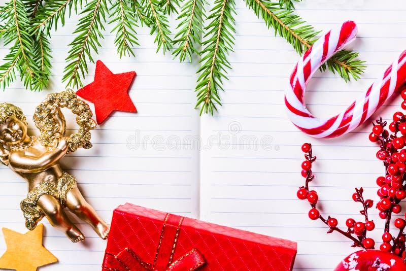 Bożenarodzeniowe jedlinowe gałąź, dekoracje, anioł, cukierek trzcina, marznąć czerwone jagody, gwiazdy i prezent pudełkowata rama fotografia royalty free
