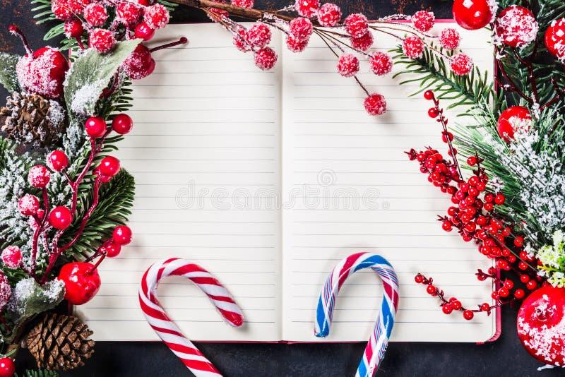 Bożenarodzeniowe jedlinowe gałąź, dekoracje, cukierek trzciny, marznąć czerwone jagody, konusują ramę na notatniku, kopii przestr zdjęcia stock