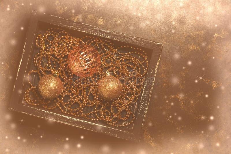 Bożenarodzeniowe piłki i koraliki w czarnym drewnianym pudełku na ciemnym nieociosanym tle Złoci Bożenarodzeniowi eleganccy roczn zdjęcia royalty free
