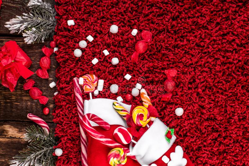 Bożenarodzeniowe skarpety pełno cukierek i cukierki na czerwonym wełnistym tle Mieszkanie nieatutowy kosmos kopii zdjęcie royalty free