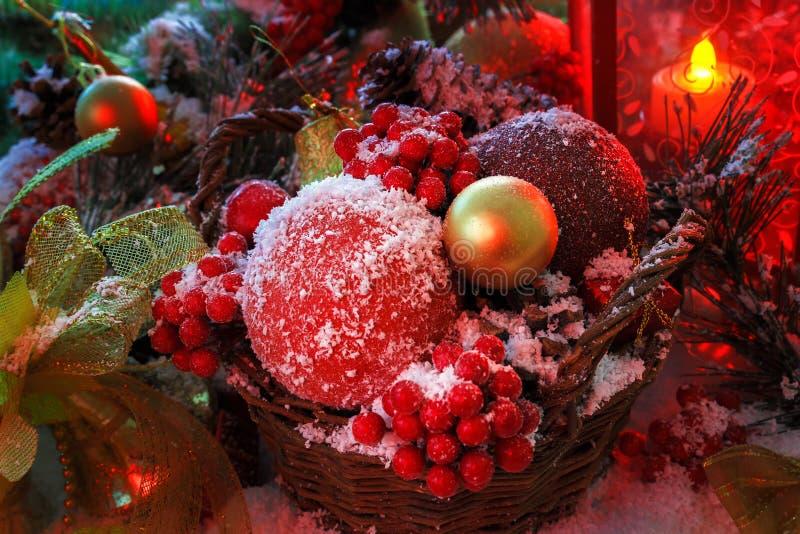 Bożenarodzeniowe zabawki w łozinowym koszu zakrywają z śniegiem w świetle czerwonego lampionu zdjęcie royalty free