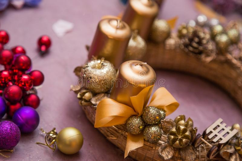 Bożenarodzeniowego dekoracji round wianku złoci kolory z świeczkami, tworzący proces z rękami i gorącym kleidłem zdjęcia stock