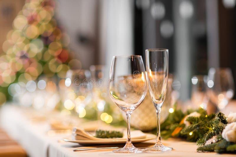 Bożenarodzeniowego gościa restauracji uczta A dekorował łomotać stół z szampańskimi szkłami i choinką w tle obrazy royalty free