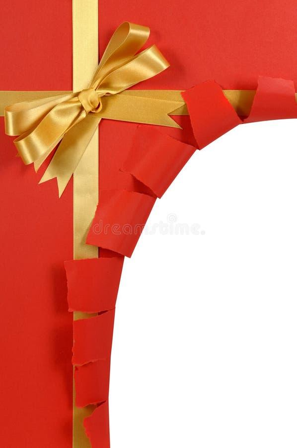Bożenarodzeniowego prezenta czerwony tło, złocisty tasiemkowy łęk, osacza poszarpanego otwiera fotografia royalty free