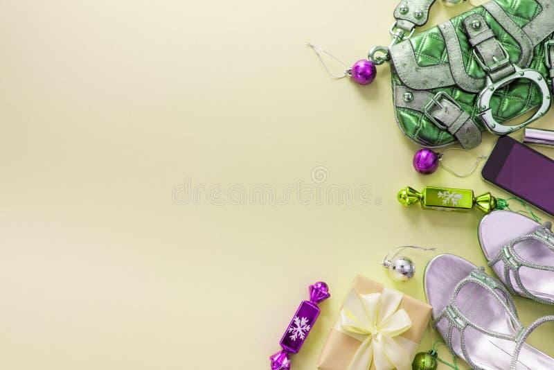 Bożenarodzeniowego tła mieszkania Lay mody akcesoriów torebki sandałów telefonu prezenta pudełka łęku żółte piłki obrazy stock