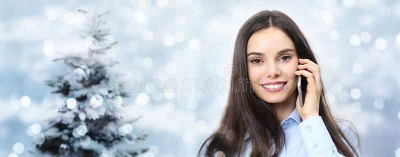 Bożenarodzeniowego tematu uśmiechnięta kobieta opowiada na telefonie, na zamazanym świetle zdjęcie royalty free