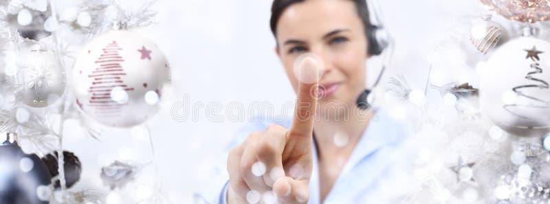 Bożenarodzeniowego tematu uśmiechnięta kobieta z słuchawki dotyka ekranem obraz royalty free