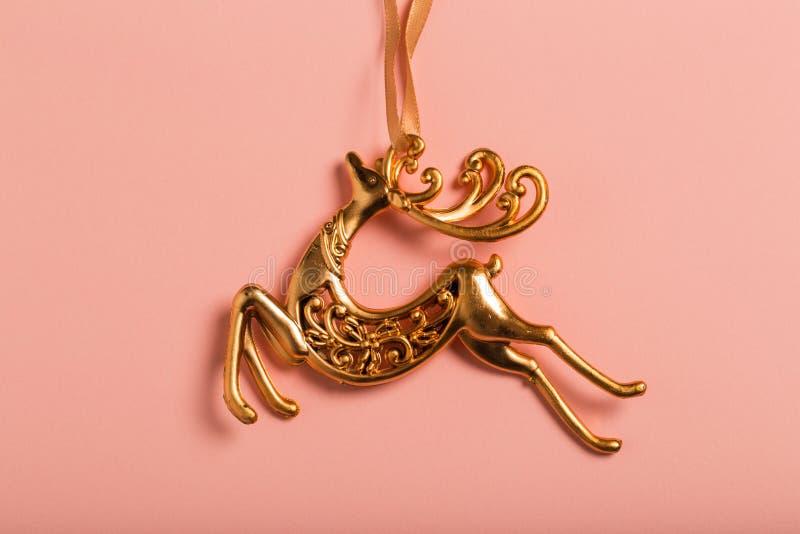 Bożenarodzeniowej dekoracji złoci rogacze na różowym tle fotografia stock