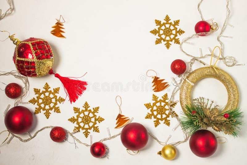 Bożenarodzeniowej teraźniejszości pudełko z czerwonym faborkiem, złocistymi dekoracjami, piłkami, płatek śniegu i światłami na bi zdjęcia royalty free