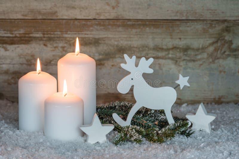 Bożenarodzeniowi biali blaski świecy z reniferową dekoracją zdjęcie royalty free