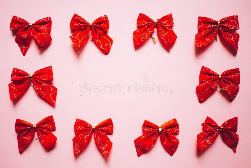 Bożenarodzeniowi czerwoni atłasowi łęki rama, set faborki na różowym tle obrazy royalty free