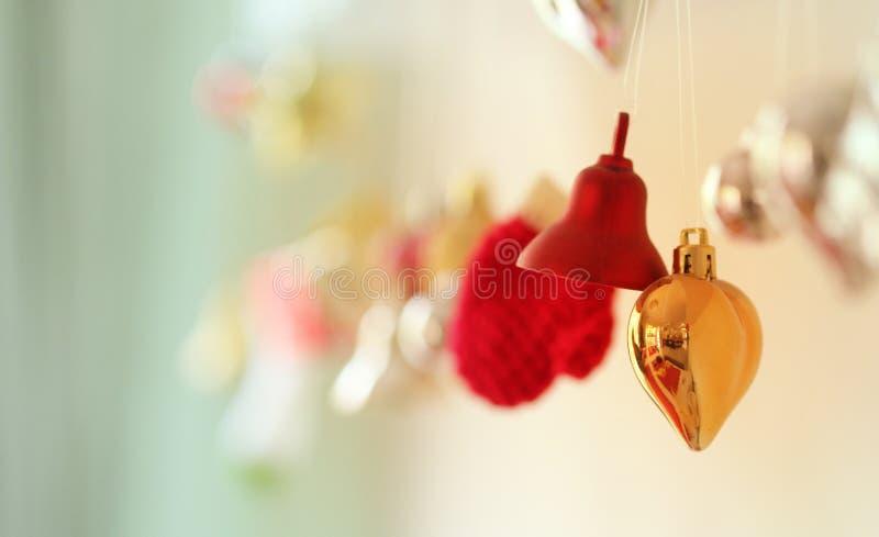 Bożenarodzeniowi dekoracja ornamenty Bell, serce i rękawiczki, kształtujemy zabawki wiesza na ścianie z plamy złota tłem obraz stock