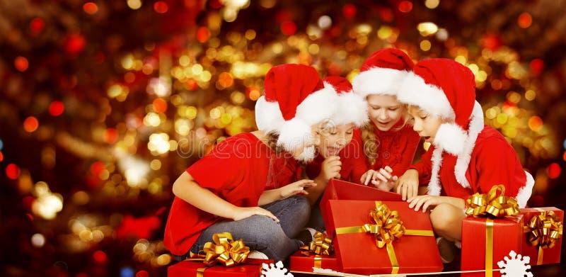 Bożenarodzeniowi dzieciaki Otwiera Teraźniejszego prezenta pudełko, dzieci w Santa kapeluszu zdjęcie royalty free