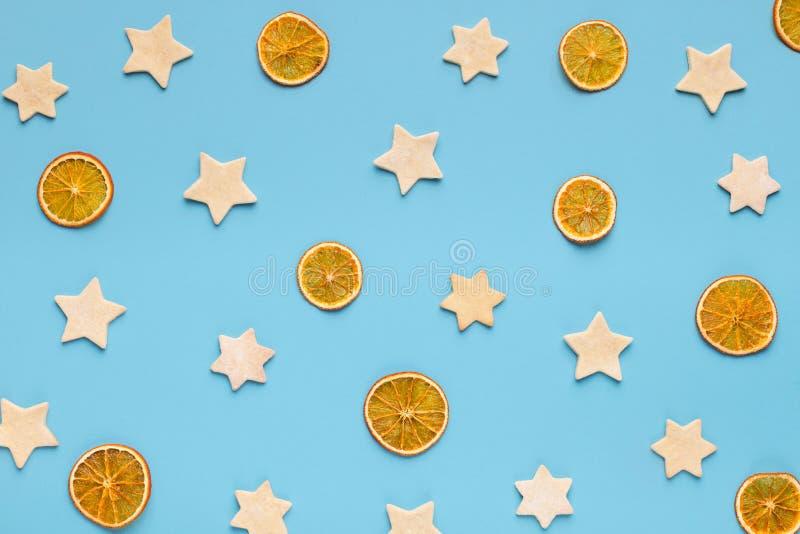 Bożenarodzeniowi imbirowi ciastka i wysuszone pomarańcze na błękitnym tle zdjęcia royalty free