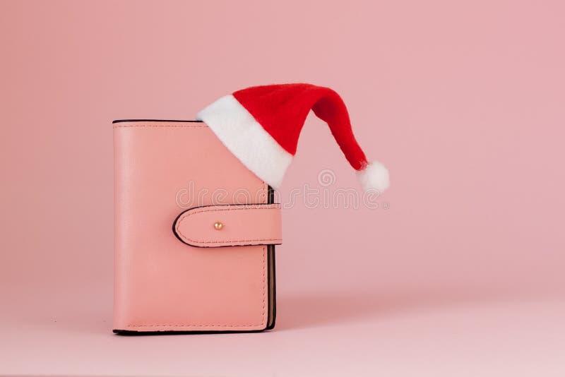 Bożenarodzeniowi koszty Różowa rzemienna kiesa z Santa Claus nakrętką, prezentem, jedlinowym drzewem i dolarami banknotów na różo obrazy stock