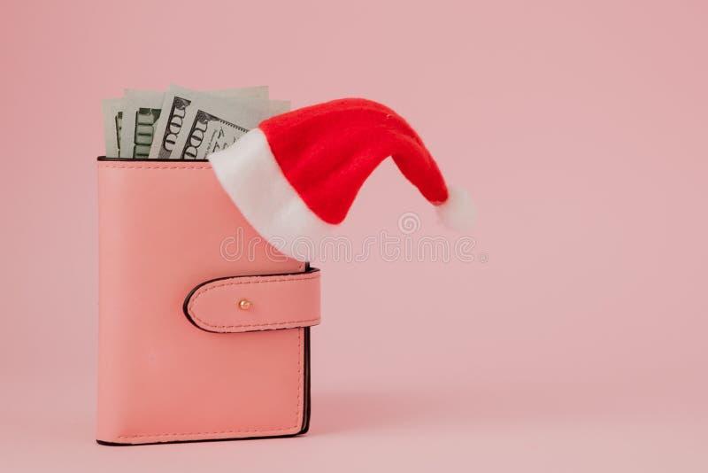 Bożenarodzeniowi koszty Różowa rzemienna kiesa z Santa Claus nakrętką, prezentem, jedlinowym drzewem i dolarami banknotów na różo fotografia royalty free