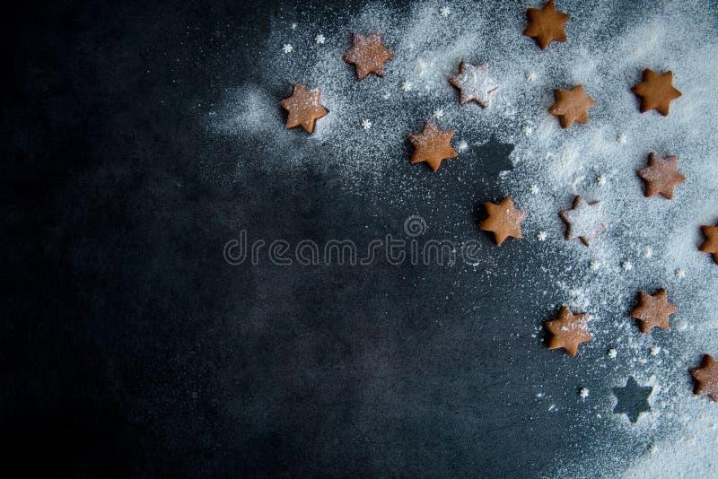 Bożenarodzeniowi miodownik gwiazdy ciastka na zmroku - błękitny tło s obraz stock