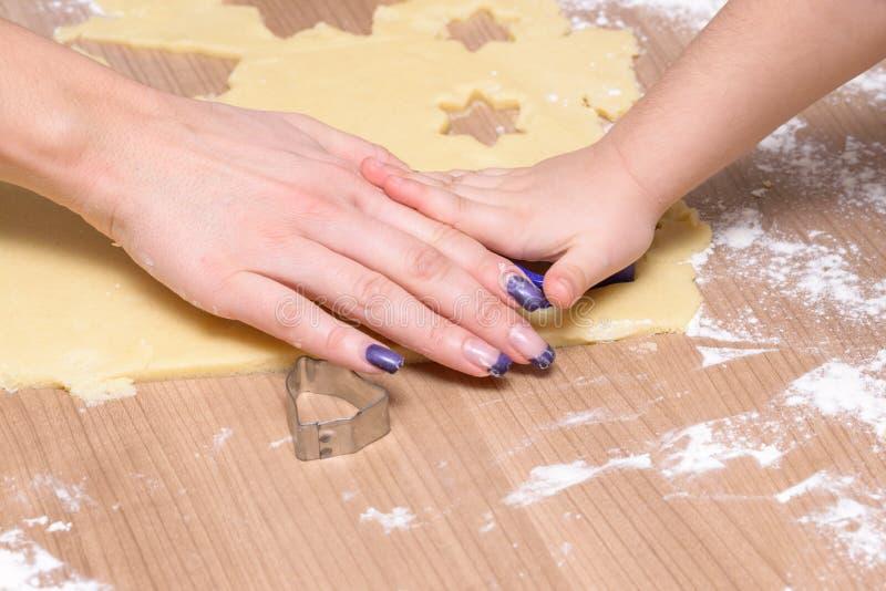 Bożenarodzeniowi pieczenia, matki i córki tnący ciastka, - ciastka wpólnie od ciasta obraz stock