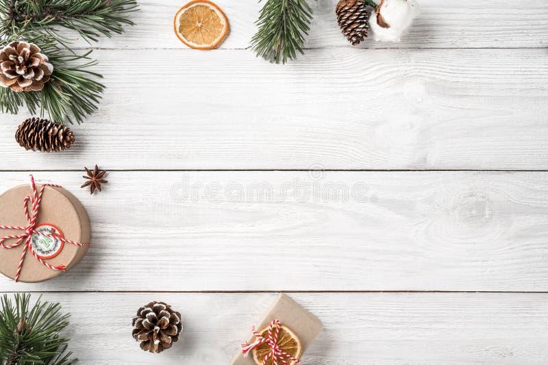 Bożenarodzeniowi prezentów pudełka na białym drewnianym tle z jodłą rozgałęziają się, sosna rożki fotografia royalty free
