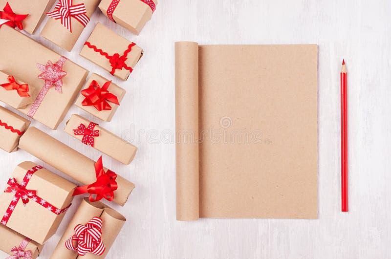 Bożenarodzeniowi prezentów pudełka z czerwonymi łękami i notatnik dla twój teksta Kraft papier na miękkiej białej drewno desce ta obraz stock