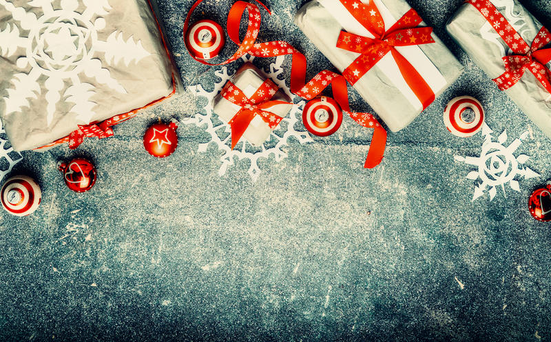 Bożenarodzeniowi prezenty, czerwone świąteczne wakacyjne dekoracje i papierowi płatki śniegu na rocznika tle, odgórny widok obrazy stock