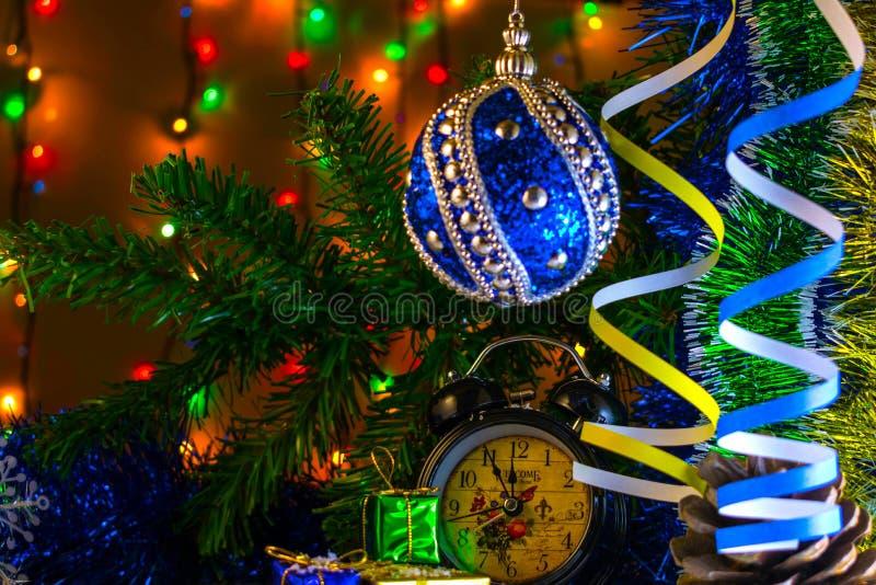 Bożenarodzeniowi prezenty i zegar z bożymi narodzeniami i zabawką na gałąź na tło girlandzie zdjęcia royalty free