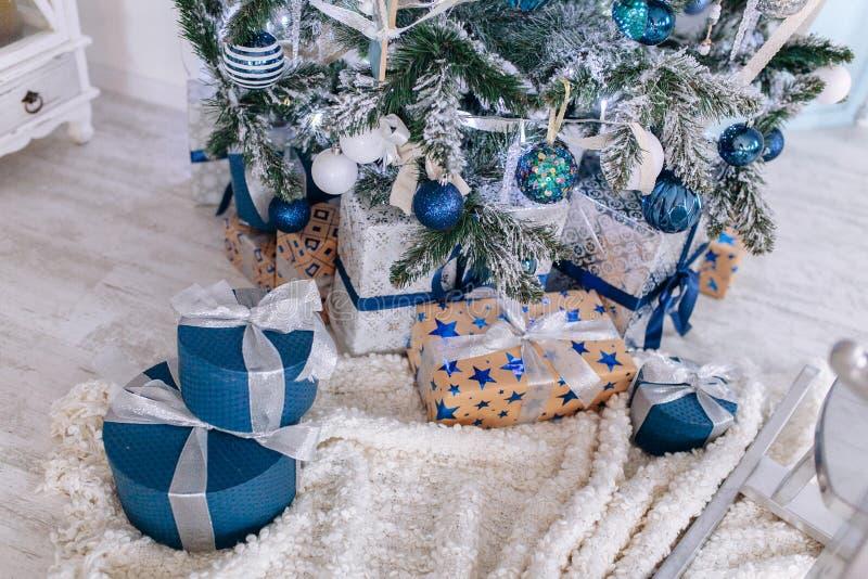 Bożenarodzeniowi prezenty zawijający w srebnym i błękitnym papierze, tło z xmas zaświecają bokeh zamazana poniższa choinka fotografia royalty free