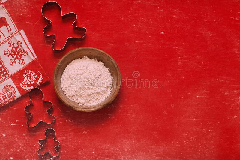 Bożenarodzeniowi składu ciastka krajacze i puchar mąka na czerwonym tle fotografia royalty free