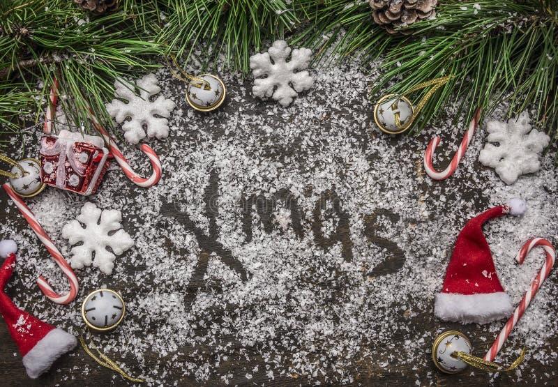 Bożenarodzeniowy śnieżny tło z słowa mas cukierkiem, kapeluszem i sosną Bożenarodzeniowymi, rozgałęzia się i sosna rożek na drewn zdjęcia stock